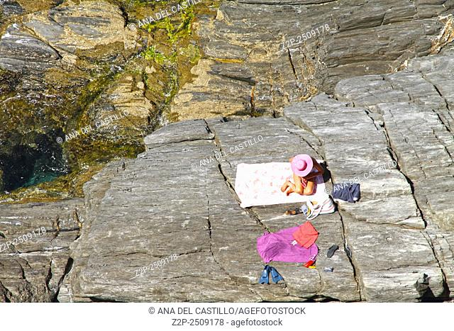 Ligurian sea from La Via dell Amore Manarola in Cinque Terre La Spezia Italy. Woman in picture hat on a rock sunbathing