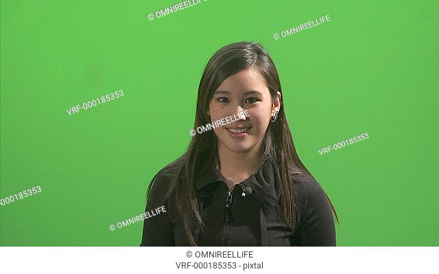 Young female with long dark hair wearing black top smiling and laughing and holding sides of head green screen