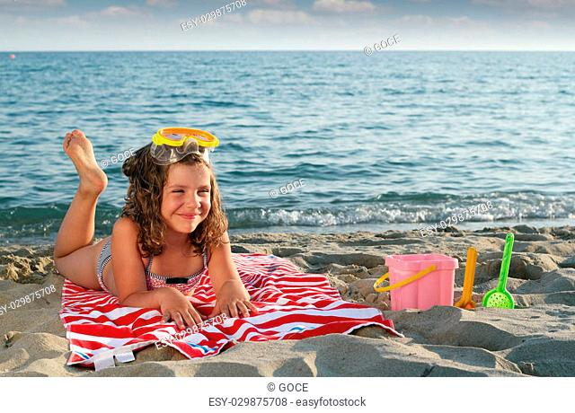 happy little girl with diving mask lying on beach