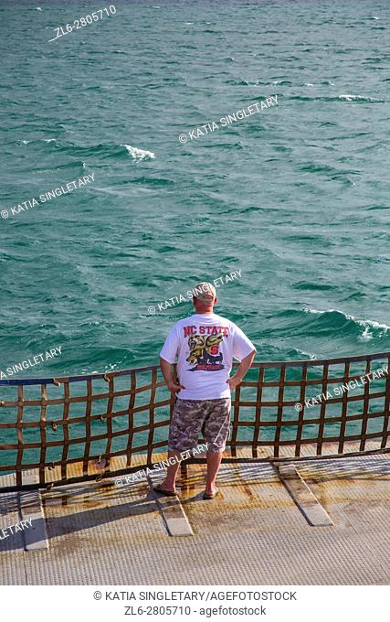 Caucasian American man with a NC State teeshirt, short and a baseball cap looking at the ocean during the crossing on the Ferry in the outer banks of North...