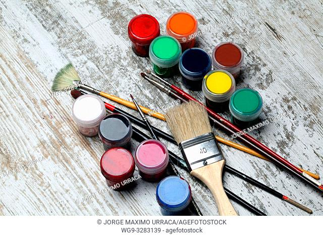 Brushes and artistic paint of different colors on artistic background