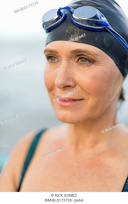 Caucasian swimmer wearing goggles and swimming cap