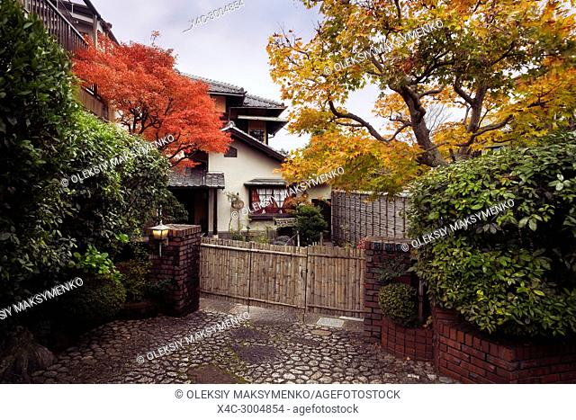 Large house with a garden in Kyoto built in traditional Japanese architectural style. Autumn scenery in Japan