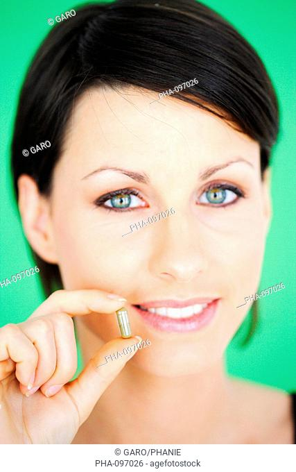 Woman with a capsule of phytotherapy food supplement