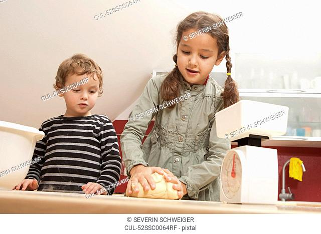 Girl kneading dough in kitchen