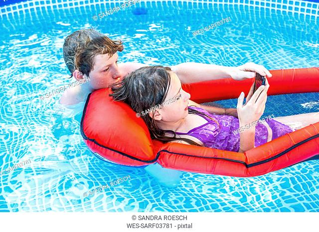 Brother and sister in swimming pool looking at smartphone
