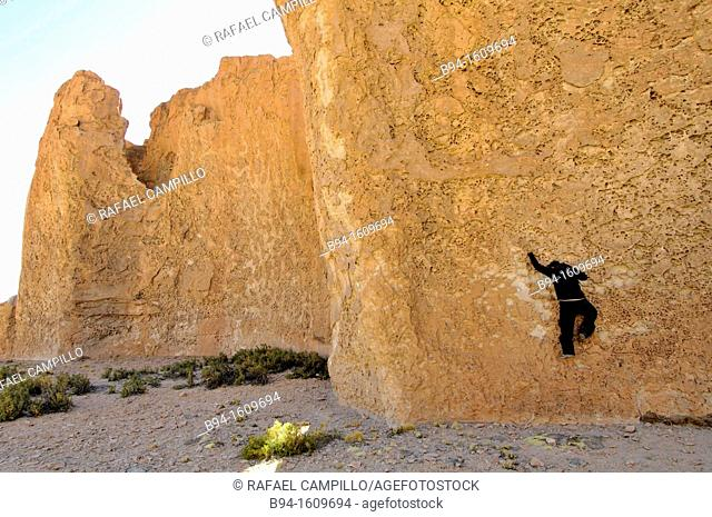 Boy climbing a wall, rocks near Oruro, Bolivia