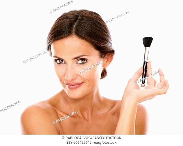 Smiling hispanic woman with make up brush for smooth her face and nude shoulders while looking at camera on isolated studio