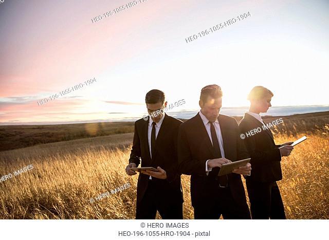 Business people using digital tablets in field