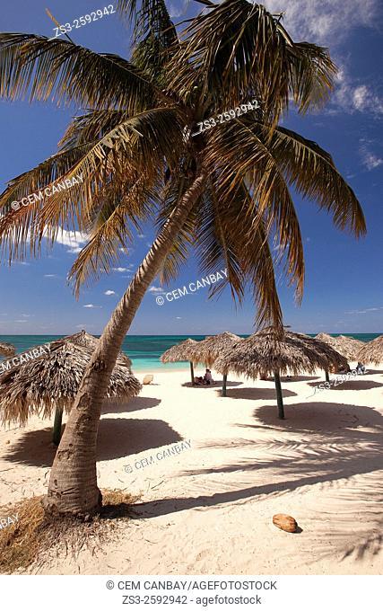 Tourists, parasols and thatched umbrellas on the beach of Playa Ancon, Trinidad, Sanctí Spíritu, Cuba, West Indies, Central America