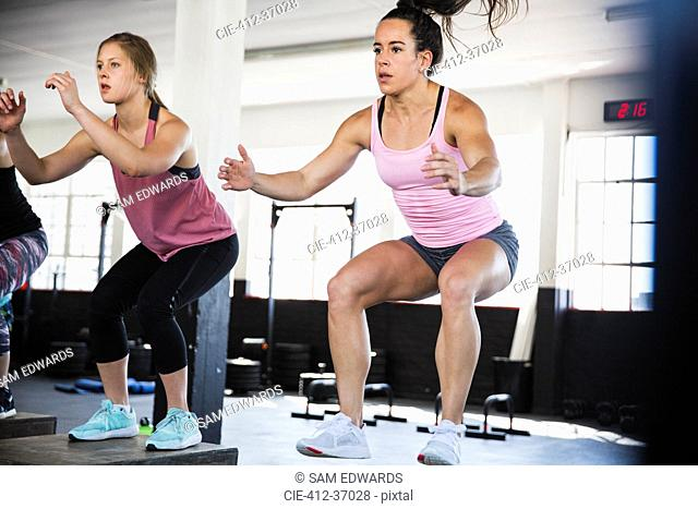Determined young women doing jump squats in exercise class