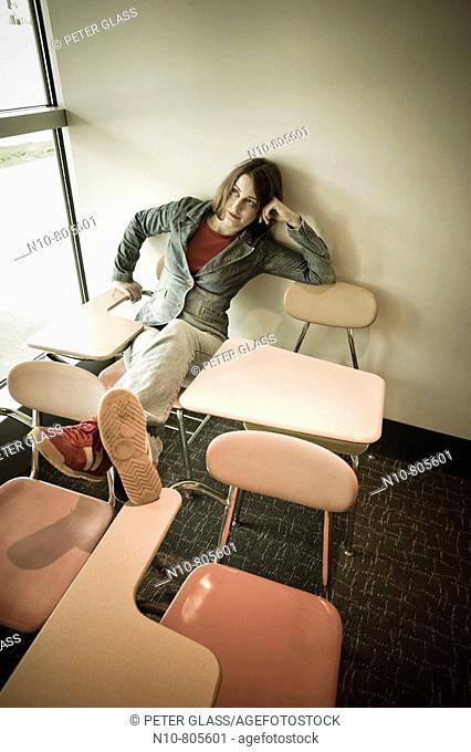 Young woman siiting in a chair by a window in a college classroom