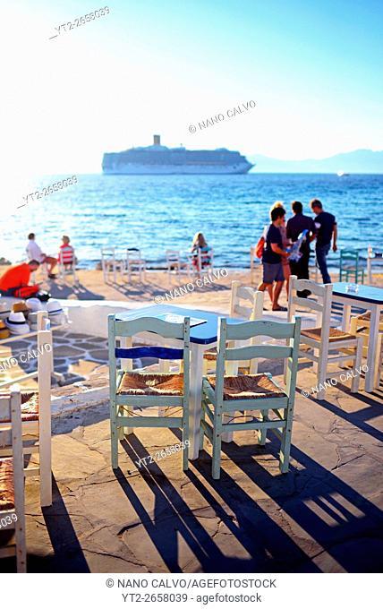 Restaurant terrace and cruise ship in view, Mykonos, Greek Islands, Greece