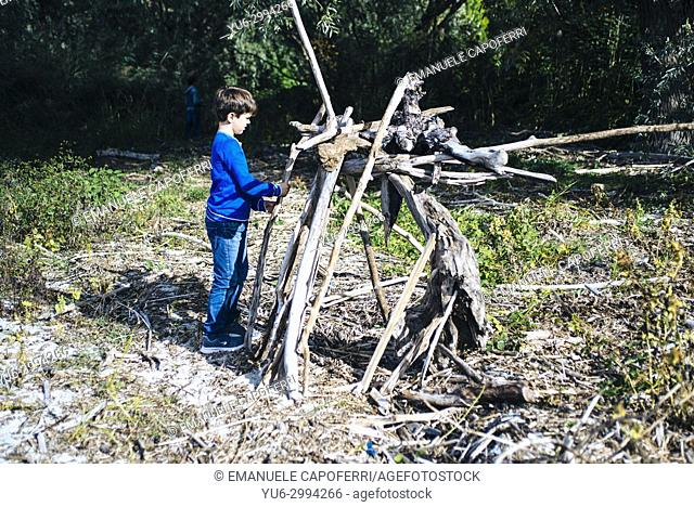child builds hut with woods of the forest. Italy