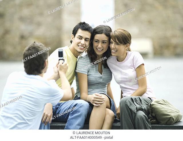Teenage boy taking photo of friends with cell phone
