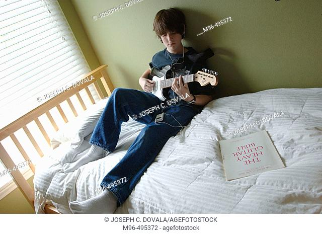 Boy playing guitar and listening to ipod