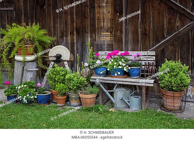 wooden bench, flowerpots, old grinding wheel in front of wooden barn