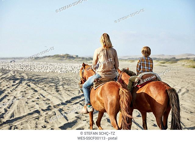 Chile, Vina del Mar, mother with son riding horses on the beach