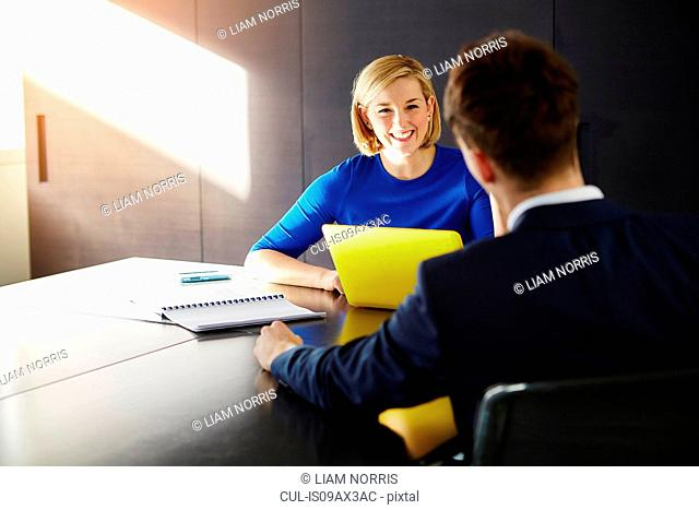 Colleagues sitting at desk having meeting smiling