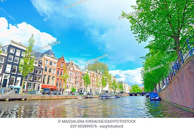 Traditional Houses and house boat along canal in Amsterdam, Holland