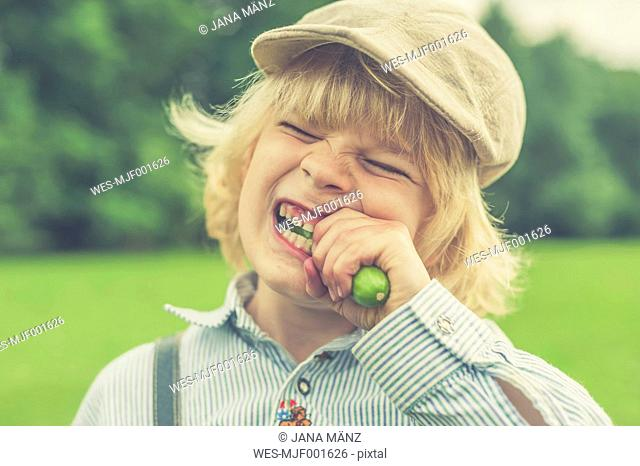 Portrait of little boy with cap eating cucumber