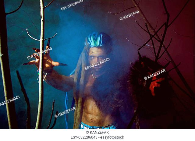 Werewolf with long nails and crooked teeth among the branches of the tree and blue smoke. Gothic image of scary diabolical creatures for Halloween