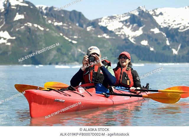 Pair of kayakers pause to take a photo as they paddle through Aialik Bay at Kenai Fjords National Park. Summer on the Kenai Peninsula