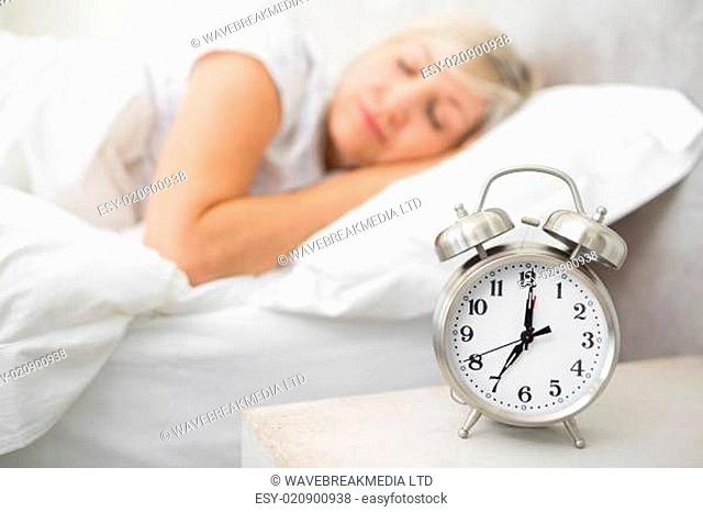 Woman sleeping in bed with alarm clock in foreground at bedroom