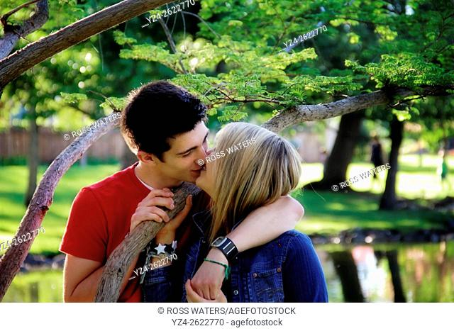Closeup of a young couple outdoors kissing