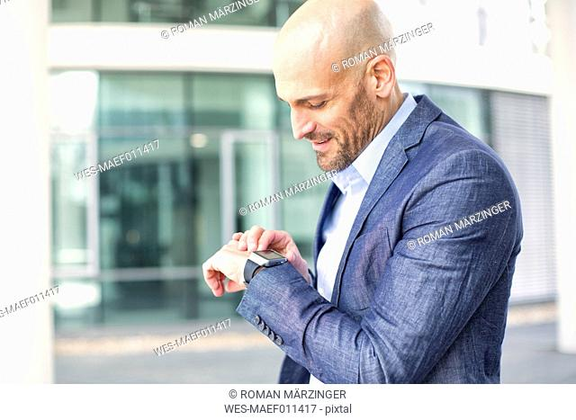 Businessman looking at smartwatch