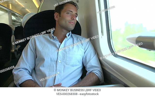 Man picking up headphones and digital tablet to listen to music on train journey .Shot on Sony FS700 in PAL format at a frame rate of 25fps