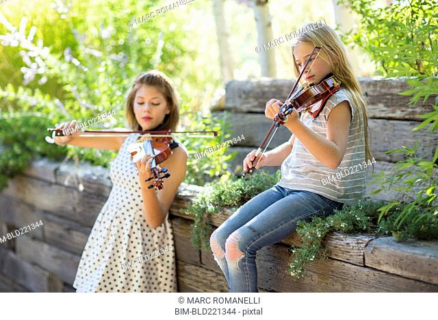 Musicians playing violins outdoors