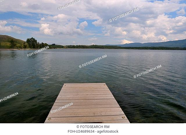 water empty boat dock jutting out lake in park