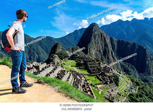 Man standing looking away at view of inca ruins, Machu Picchu, Cusco, Peru, South America