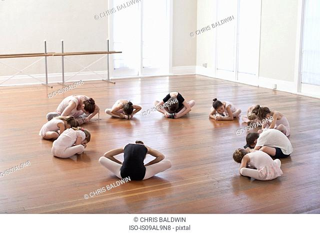 Children sitting on floor practicing ballet with teacher in ballet school