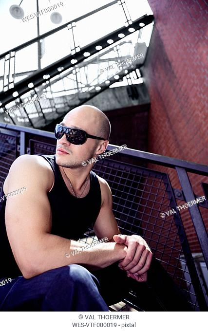 Man with bald head and sunglasses sitting outdoors