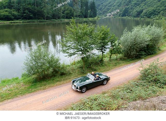 Green vintage car MG driving along a river