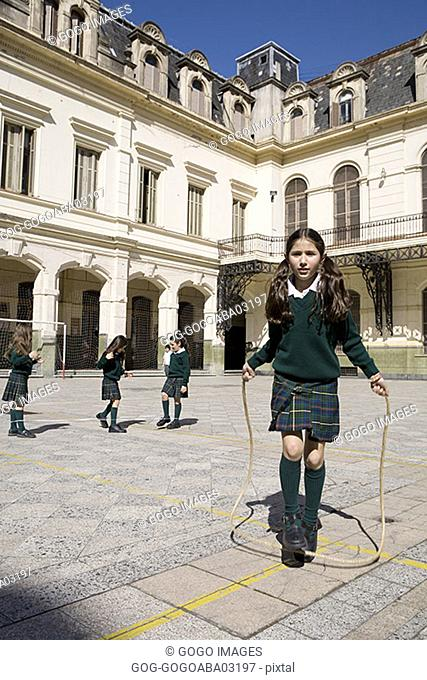 Young student jumping rope in courtyard