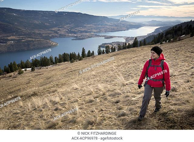 Young woman in pink jacket hiking and happy