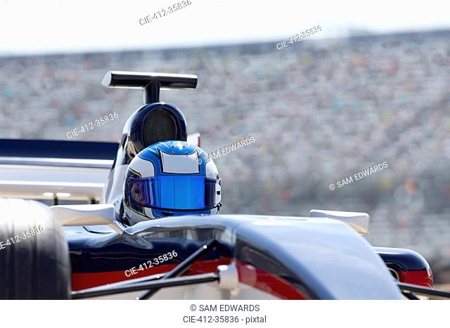 Formula one race car driver wearing helmet on sports track