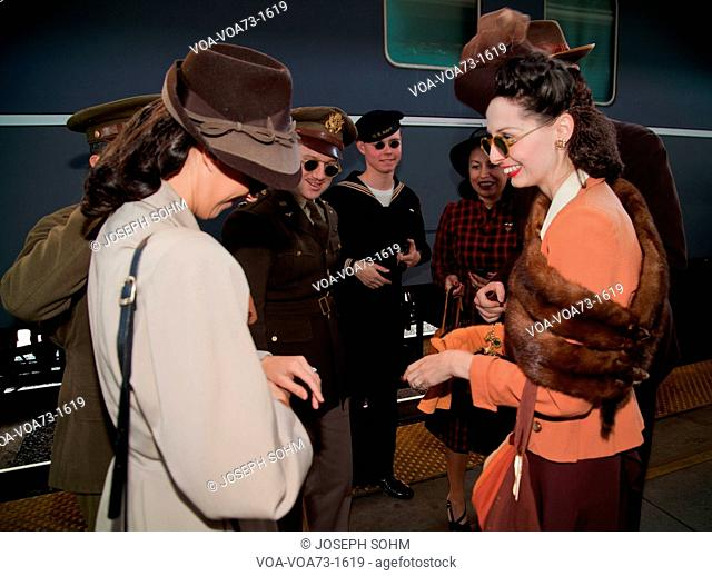 Two 1940's female reenactors laugh before boarding Pearl Harbor Day Troop train reenactment from Los Angeles Union Station to San Diego