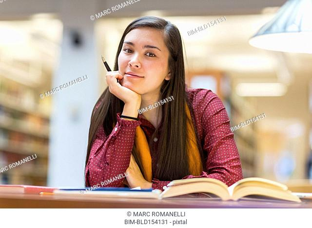 Mixed race student working in library