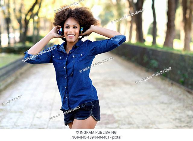Young black woman with afro hairstyle listening to the music with headphones in urban background. Mixed funny woman wearing blue shirt and shorts