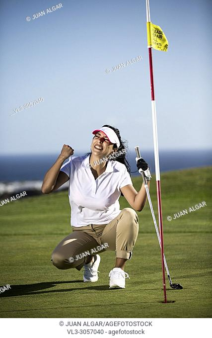 Woman in sportswear holding fist up having goal while playing golf on course