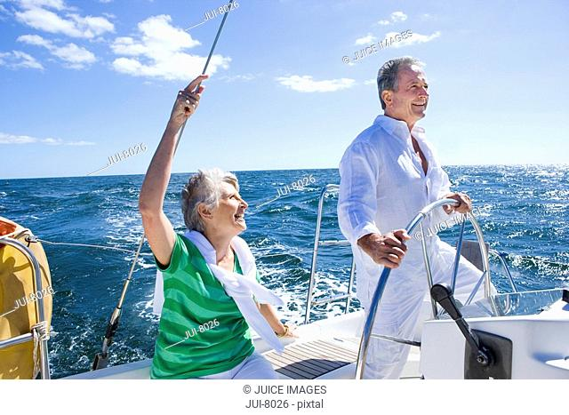 Mature couple sailing out at sea, man standing at helm of yacht, steering, woman looking on, smiling, side view