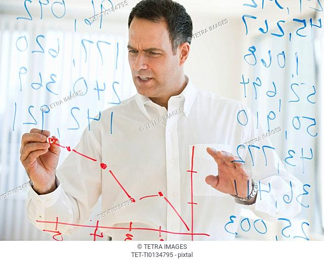 Mature businessman drawing line graph on transparent glass wall