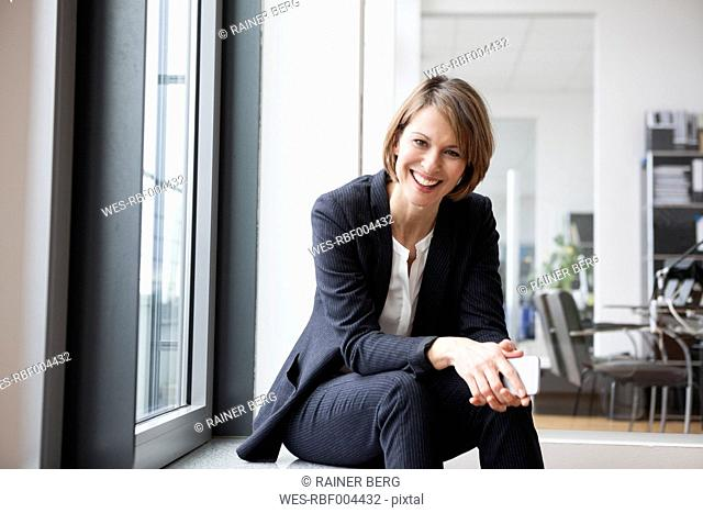 Smiling businesswoman sitting at the window