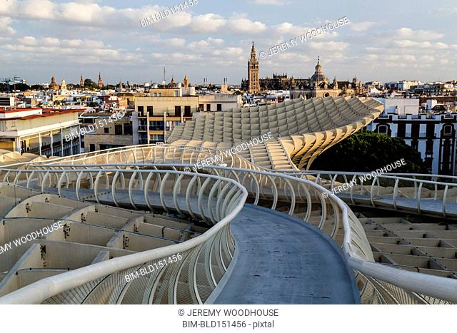 Curving footbridge and Seville cityscape, Andalusia, Spain