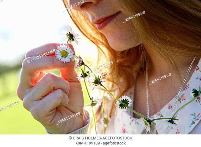 Girl holding daisy chain outside in the sunshine