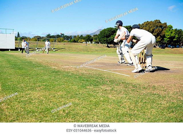 Cricket players playing match at field